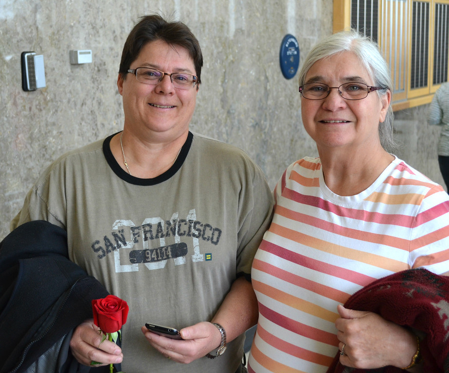 """. Debora Renner, left, holds a rose as she and partner Faith Robinson stand in line for a marriage license at the Oakland County Courthouse on Saturday morning. The two have been together 35 years. \""""It\'s wonderful,\"""" says Robinson. Dustin Blitchok-The Oakland Press"""