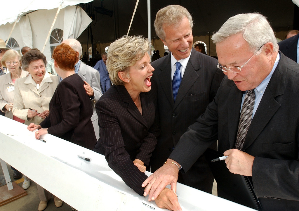 """. Michigan Governor Jennifer Granholm, third from right, lets out a laugh after Oakland County Executive L. Brooks Patterson, far right, signed his name on a construction beam, with the abbreviated word \""""Gov.\"""" under his own name.  Photo taken on Wednesday, July 14, 2004, at Fox Run retirement community in Novi, Mich.  Standing in between them is City of Novi Mayor Lou Csordas.  The beam, signed by guests in attendance, will be the first used in construction of Fox Run�s fifth residential building.  Granholm visited Fox Run as a stop on her tour of the state for Economic Development"""
