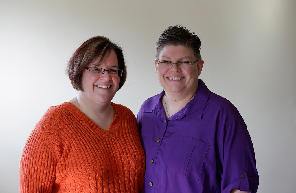. FILE - In this March 5, 2013, file photo, April DeBoer, left, and Jayne Rowse pose at their home in Hazel Park, Mich. A federal judge has struck down Michigan\'s ban on gay marriage Friday, March 21, 2014, the latest in a series of decisions overturning similar laws across the U.S. The two nurses who\'ve been partners for eight years claimed the ban violated their rights under the U.S. Constitution. (AP Photo/Paul Sancya, File)
