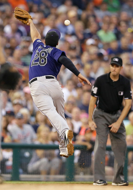 . Colorado Rockies third baseman Nolan Arenado stretches but is unable to stop a double by Detroit Tigers\' Eugenio Suarez during the fifth inning of an interleague baseball game, Friday, Aug. 1, 2014, in Detroit. (AP Photo/Carlos Osorio)