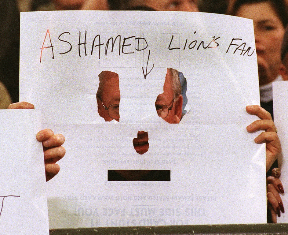 ". West Bloomfield\'s Mike Fleisher hides his face behind this homemade sign reading ""Ashamed Lions Fan\"", that he made from a seat card used to spell out Thank You American for the halftime show, late in the Detroit Lions 29-27 loss to the Green Bay Packers Thursday at the Pontiac Silverdome."