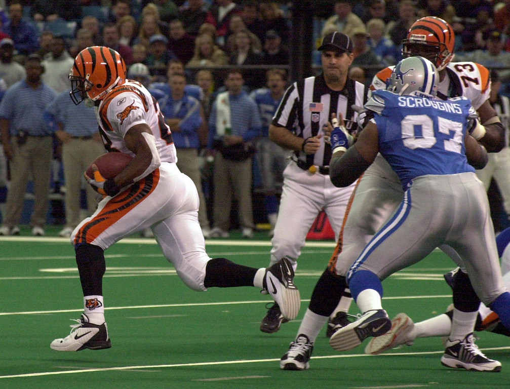 . Corey Dillon (28) of the Cincinnati Bengals slips past Tracy Scroggins (97) of the Detroit Lions for a 96 yard touchdown run in the first quarter during Sunday\'s game played at the Pontiac Silverdome. The Lions lost 31-27 to the Bengals.