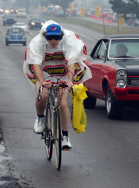 . Harvey Smith, of Washington D.C., does his best to stay dry during the 2006 Woodward Dream Cruise in Royal Oak.
