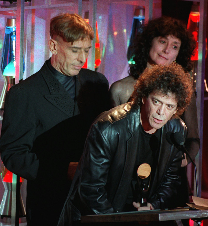 . FILE -  In this Jan. 17, 1996 file photo, Lou Reed takes the podium as the Velvet Underground, the group he once headed, is inducted into the Rock and Roll Hall of Fame during a ceremony in New York s Waldorf-Astoria Hotel. Band mate John Cale is at left, and at right is Martha Morrison, accepting for late band member Sterling Morrison. Punk-poet, rock legend Lou Reed is dead of a liver-related ailment, his literary agen said Sunday, Oct. 27, 2013. He was 71. (AP Photo/Mark Lennihan, File)