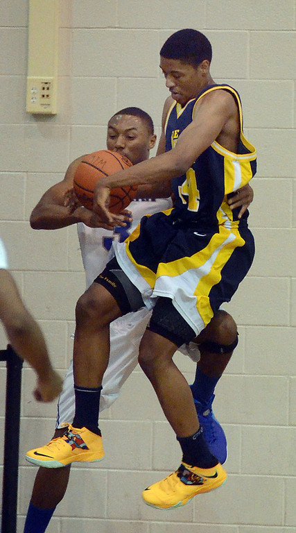 . Walled Lake Western\'s #3 Marcus Bailey Jr. (left) and Detroit Country Day\'s #34 DeShawn Lewis chase down a loose ball during their game at Walled Lake Western High School, Friday December 13, 2013. (Vaughn Gurganian-The Oakland Press)
