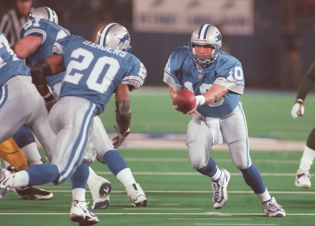 . Detroit Lions quarterback Charlie Batch (right, #10) hands off the ball to teammate Barry Sanders (#20) during second half action against the Green Bay Packers, Thursday, October 15, 1998, at the Pontiac Silverdome in Pontiac, Mich.