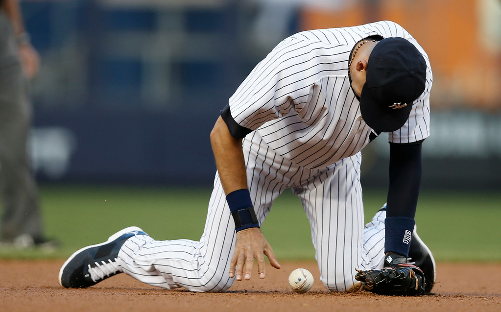 . New York Yankees shortstop Derek Jeter (2) commits an error as he misplays Rajai Davis\'s ground ball in the first inning of  a baseball game against the Detroit Tigers at Yankee Stadium in New York, Wednesday, Aug. 6, 2014. Davis reached on the error. (AP Photo/Kathy Willens)
