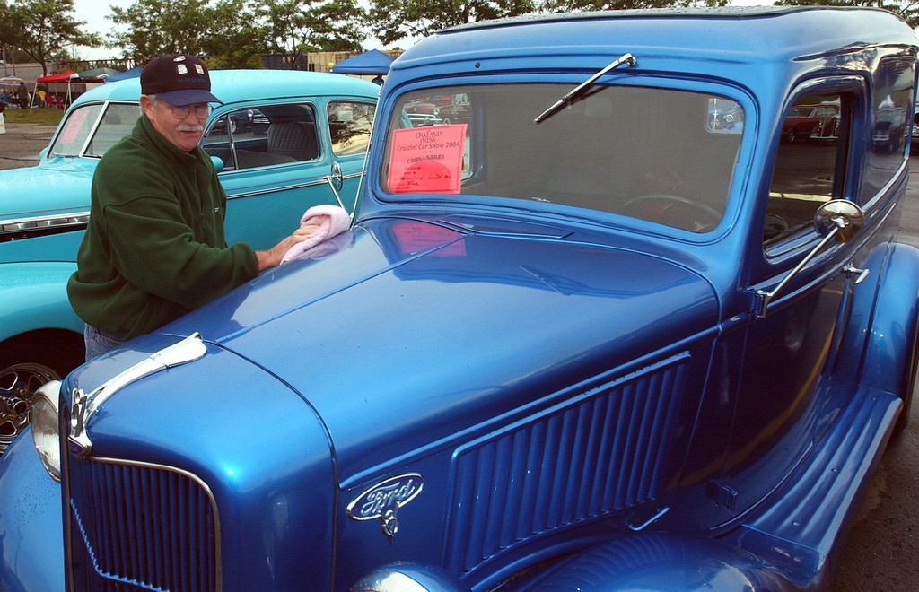 . Bob Brannan of Evart wipes the rain drops of his classic 1936 Ford on display in the parking lot of the Phoneix Plaza in downtown Pontiac during Friday night\'s Woodward Dream Cruise. The annual classic cruise goes from Pontiac to Ferndale covering 16-miles of classic cars, food & entertainment along the way.