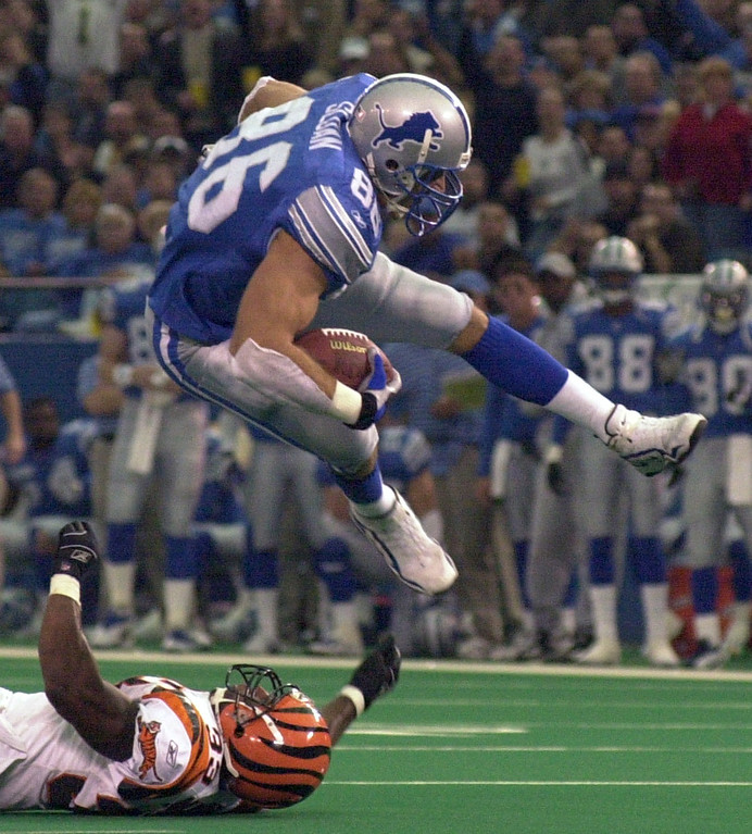 . Detroit Lions tight end David Sloan (86) goes airborn after getting hit by Cincinnati player JoJuan Armour (33) during Sunday\'s game played at the Pontiac Silverdome. The Lions lost 31-27 to the Bengals.