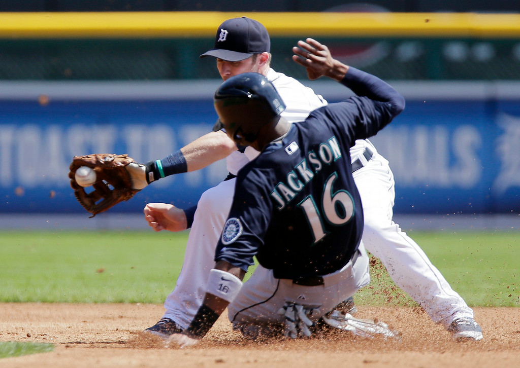 . Seattle Mariners\' Austin Jackson beats the pickoff throw to Detroit Tigers shortstop Andrew Romine to steal second base during the second inning of a baseball game on Sunday, Aug. 17, 2014, in Detroit. (AP Photo/Duane Burleson)