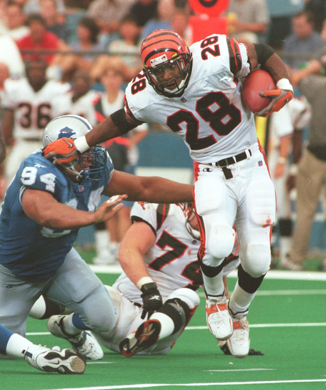 . Detroit Lions Luther Elliss (94) tries to make a tackle on Corey Dillion (28) of the Cincinnati Bengals during the 3rd quarter of Sunday\'s game played at the Pontiac Silverdome.