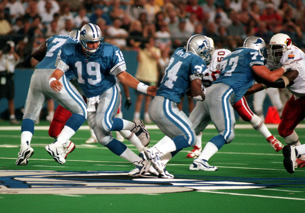 . Detroit Lions quarterback Scott Mitchell (19) hands the ball off to Ron Rivers (34) during the first quarter of the preseason home opener against the Arizona Cardinals.