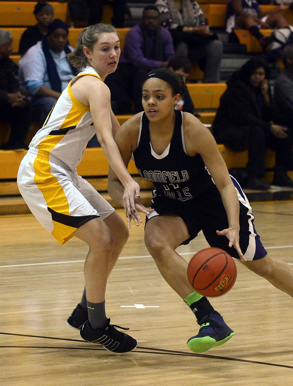 . Bloomfield Hills #11 Shannon Wilson drives to the basket past Rochester Adams #11 Jenny Rosonke during their game at Rochester Adams High School, Thursday January 30, 2014.  Adams went on to win the game 56-50. (Vaughn Gurganian-The Oakland Press)