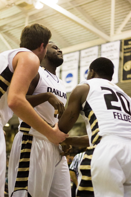 . Oakland forwards Lloyd Neely and Corey Petros help Kahlil Felder to his feet after a fall Tuesday, Oct. 29, 2013 at the Athletics Center O\'rena. Photo by Dylan Dulberg