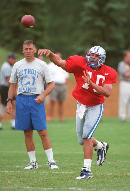 . Detroit Lions quarterback Charlie Batch (right,#10) makes a pass during practice, held at Saginaw Valley State University, Monday, August 9, 1999.  Man at left is unidentified.