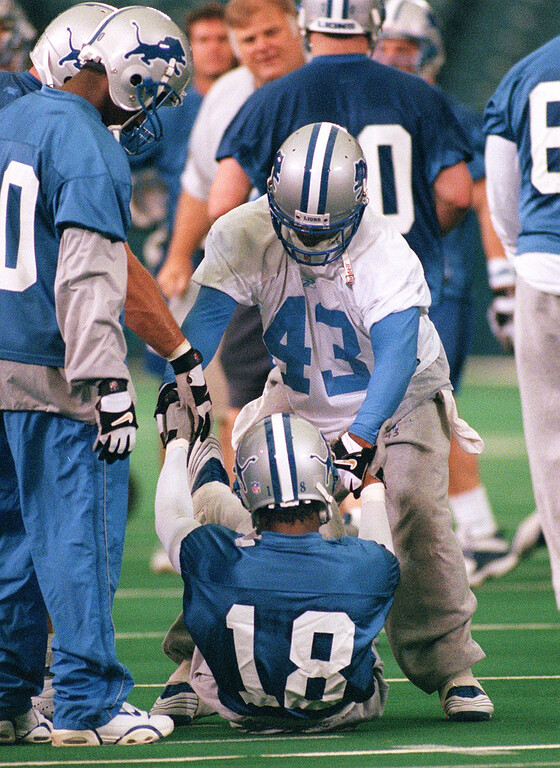 . Detroit Lions wide receiver and draft pick Scotty Anderson (bottom, #18) gets picked up by teammate Ligarius Jennings (#43) after hurting his foot while being tackled during minicamp, held inside the Silverdome in Pontiac, Mich., Friday, June 1, 2001.