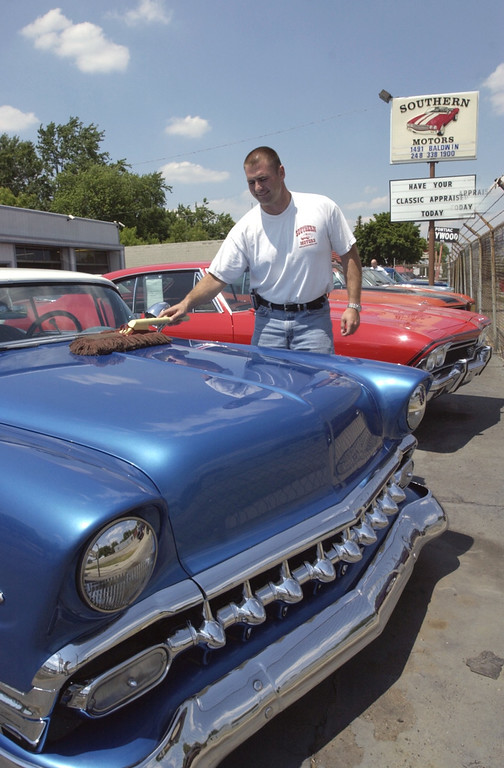 . Sales manager Dave Witt feathers off the dust on this \'56 Chevy BelAir. His company, Southern Motors is participating in the first-ever auction during the Woodward Dream Cruise.