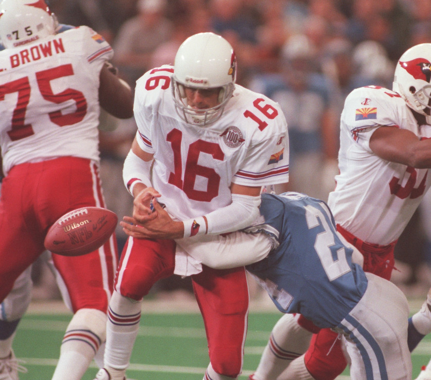 . Detroit Lions cornerback Kevin Abrams (right, #24) sacks Arizona Cardinals quarterback Jake Plummer (#16) and forces a fumble during first quarter action at the Pontiac Silverdome.  Plummer recovered the fumble.
