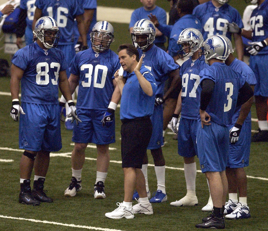 . Detroit Lions head coach Steve Mariucci, center, works with some of the offense players during Thursday\'s mini-camp held at the Detroit Lions practice facility in Allen Park
