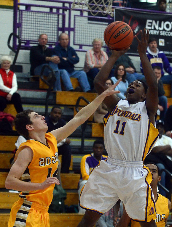 . Avondale\'s #11 Chris Barton goes up for a shot while defended by Rochester Adams #14 Cole Davis during their game at Avondale High School, Tuesday December 11, 2013. (Vaughn Gurganian-The Oakland Press)