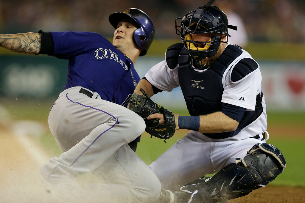 . Colorado Rockies\' Brandon Barnes safely slides under the tag of Detroit Tigers catcher Bryan Holaday during the seventh inning of an interleague baseball game, Friday, Aug. 1, 2014, in Detroit. (AP Photo/Carlos Osorio)