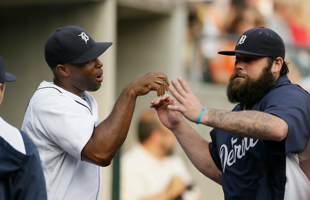 . Detroit Tigers right fielder Torii Hunter, left, and relief pitcher Joba Chamberlain exchange handshakes in the dugout before the first inning of an interleague baseball game against the Colorado Rockies, Friday, Aug. 1, 2014, in Detroit. (AP Photo/Carlos Osorio)