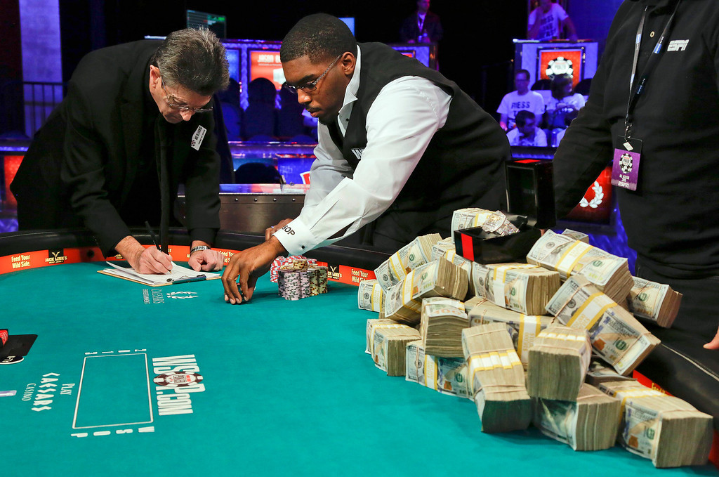 . The dealer and a poker official count Ryan Riess\' chips before the start of the last table of the World Series of Poker, Tuesday, Nov. 5, 2013, in Las Vegas. (AP Photo/Julie Jacobson)