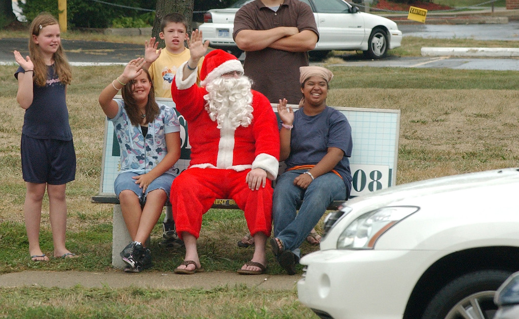 . An unidentified group of car enthusiasts, including Santa Claus, wave to motorists making the loop on Woodward, during the Dream Cruise.  Photo taken on Saturday, August 21, 2010, in Pontiac, Mich.  (The Oakland Press/Jose Juarez)
