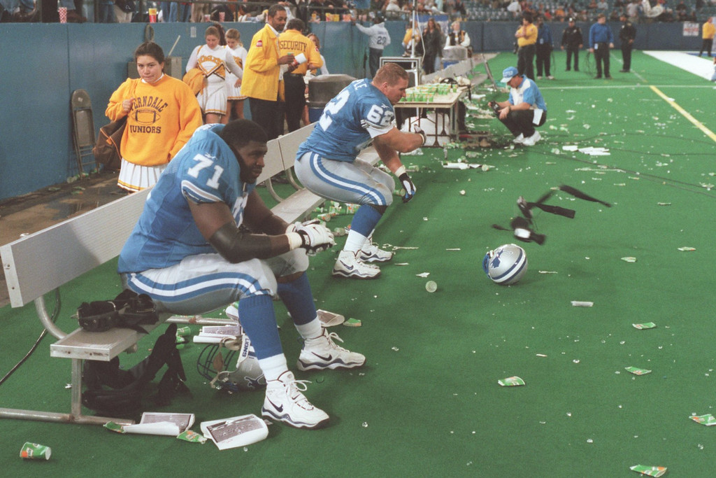 . Detroit Lions #71 tackle Larry Tharpe sits on an empty bench while #62 guard Tony Semple throws a piece of his equipment after a disappointing lost.The Arizonia Cardinals beat the Detroit Lions 17-15 in the Pontiac Silverdome.