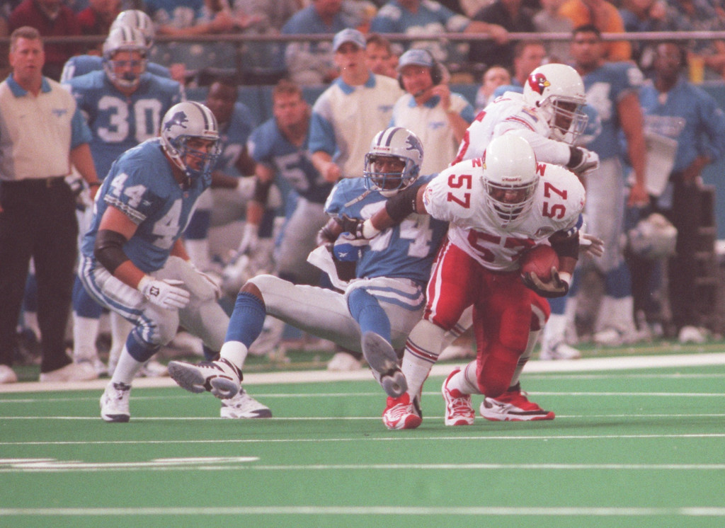 . Arizona Cardinals middle linebacker Ronald McKinnon (right, #57) intercepts a pass in front of Detroit Lions players Tommy Vardell (left, #44) and Herman Moore (#84) during the first quarter at the Pontiac Silverdome.