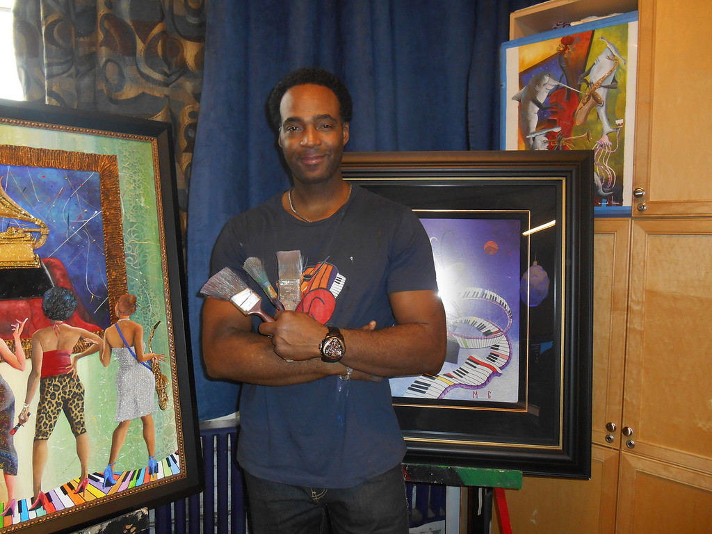 . Marcus Glenn poses with some of his paintings in his Corktown studio in Detroit. Photo by Nicole M. Robertson