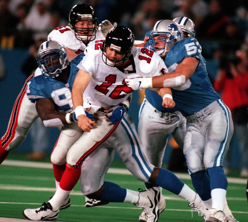 . Detroit Lions defensemen Robert Porcher (left, #91) and Rob Fredrickson (#53) take down Atlanta Falcons quarterback Chris Chandler (#12).