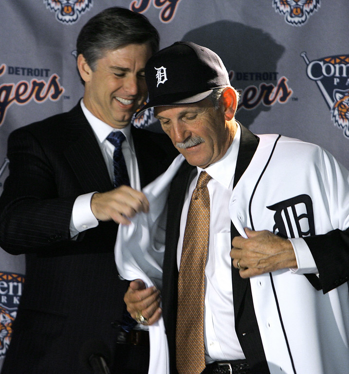 . Detroit Tigers president and general manager Dave Dombrowski, left, helps new manager Jim Leyland with a Tigers jersey while being introduced as the teams manager in Detroit, Tuesday, Oct. 4, 2005. The Tigers hired Leyland as their manager to replace Alan Trammell, fired a day earlier after three seasons. (AP Photo/Paul Sancya)