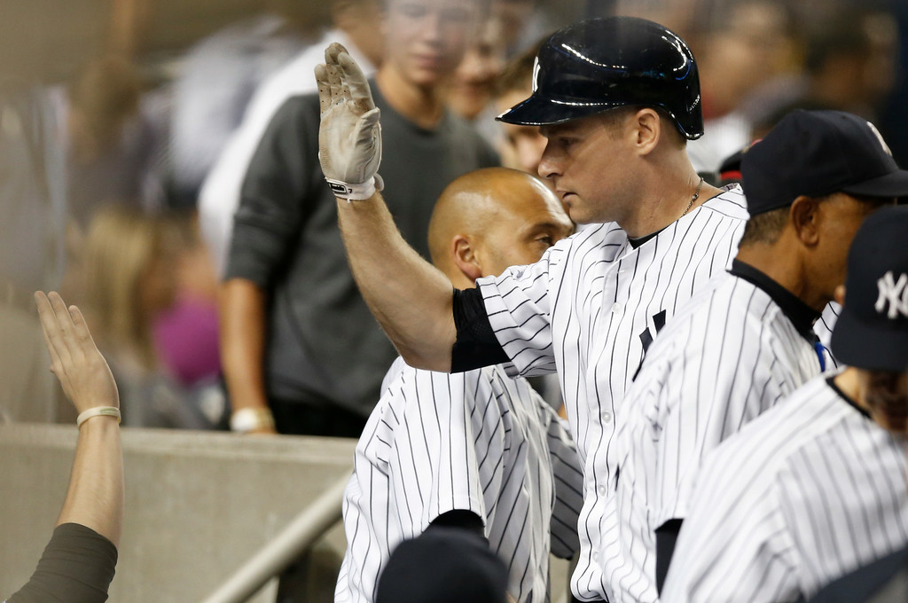 . New York Yankees Chase Headley greets teammates after hitting a fifth-inning, solo home run off Detroit Tigers starting pitcher Justin Verlander in a baseball game at Yankee Stadium in New York, Wednesday, Aug. 6, 2014.  (AP Photo/Kathy Willens)