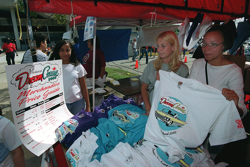 . Karessa Spudowski, left, and Crystal Allen sell Dream Cruise T-Shirts to help raise money for the Americorps from the parking lot of the Phoenix Plaza during Friday night\'s kick-off of this year\'s Woodward Ave. Dreram Cruise in Pontiac.