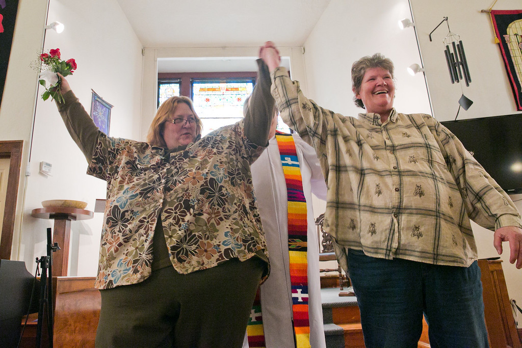 """. Stacy Rutz, left, and Maryann Day, right, hold their arms up after Rev. Bill Freeman announces the couple married during their wedding ceremony at the Harbor Unitarian Universalist church in Muskegon on Saturday, March 22, 2014. Day and Rutz said they\'ve been together for 14 years. \""""We\'ve been through a lot, hard times times and good times,\"""" Day said during her vows. \""""You\'ve helped me raise my children, you\'ve supported me in every decision I\'ve made. I will love you until the day that I close my eyes.\"""" (AP Photo/The Chronicle, Natalie Kolb)"""
