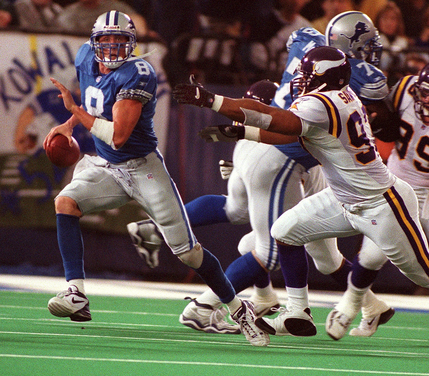 . Detroit Lions quarterback Mike McMahon (left) scrambles away from Minnesota Vikings\' Talance Sawyer during the team\'s 27-24 victory over the Minnesota Vikings at the Silverdome Sunday.  The Lions are now 1-12.