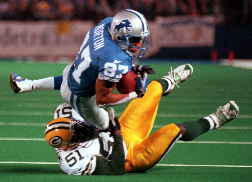 . Detroit Lions reciever Johnnie Morton (87) is brought down by Brian Williams of the Green Bay Packers during Thursday\'s night\'s game at the Pontiac Silverdome.