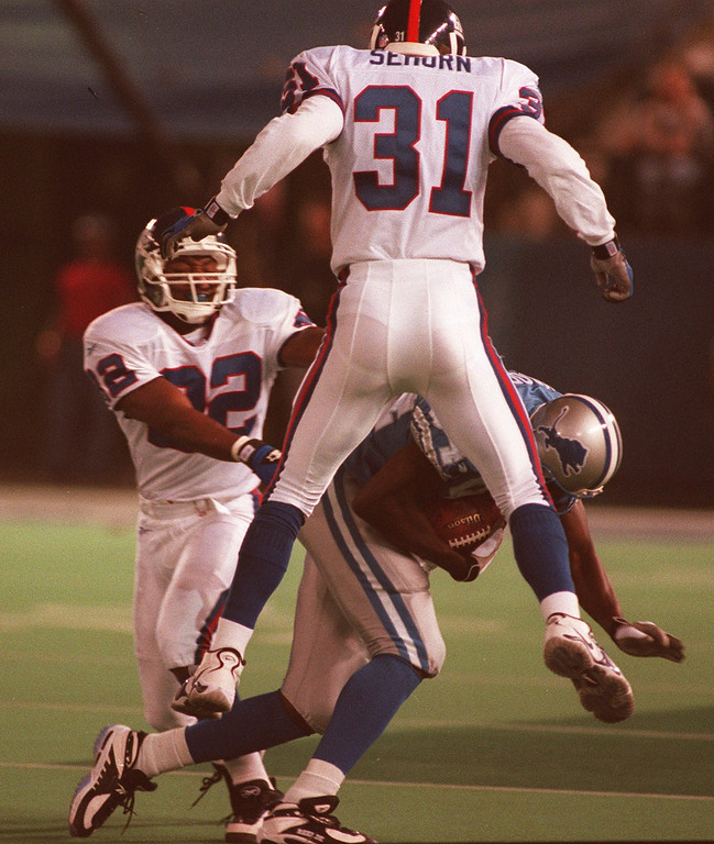 . Hermon Moore (84) of the Detroit Lions picks up a key first down against Phillippi Sparks (22) and Jason Sehorn (31) to keep the Lions drive alive late in the second half against the New York Giants.