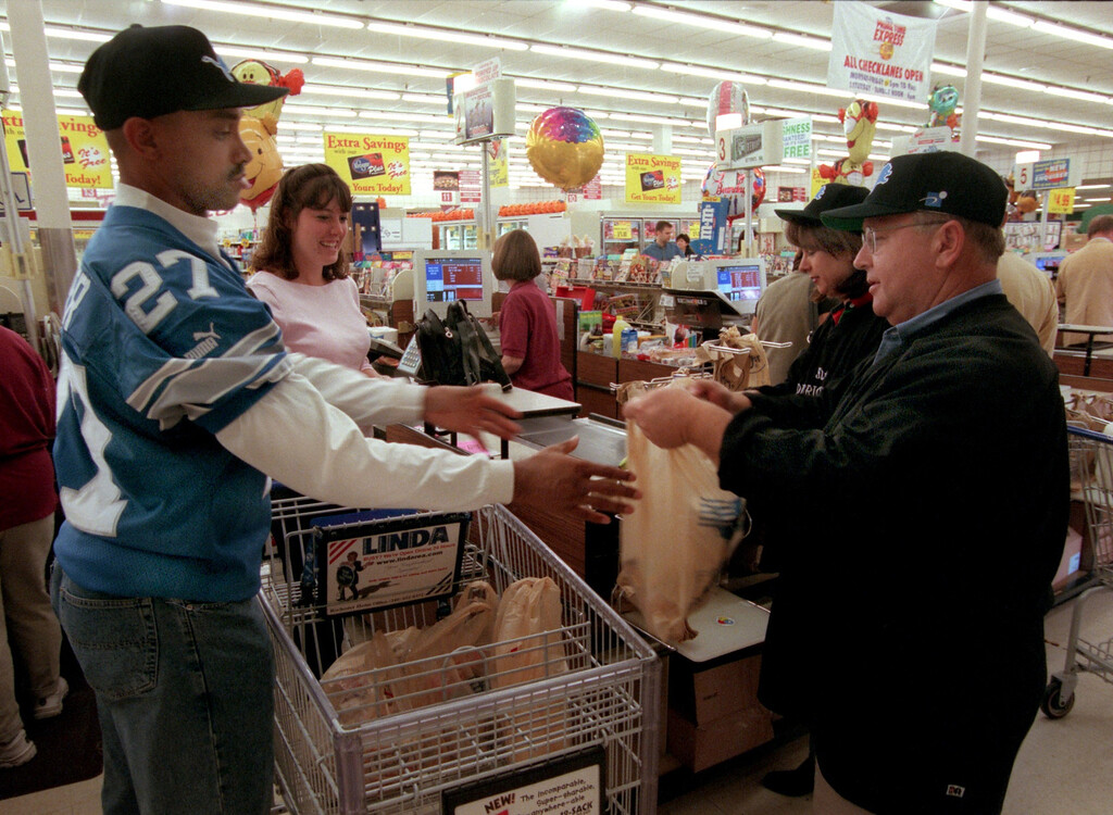 . Detroit Lions defensive captian, Mark Carrier and 51st District Judges,  Julie Nicholson, and Ralph Nelson bag groceries for an Oakland University student Julie Lambert as part of a contest to raise funds for substance abuse at the Kroger store in Rochester Hills.