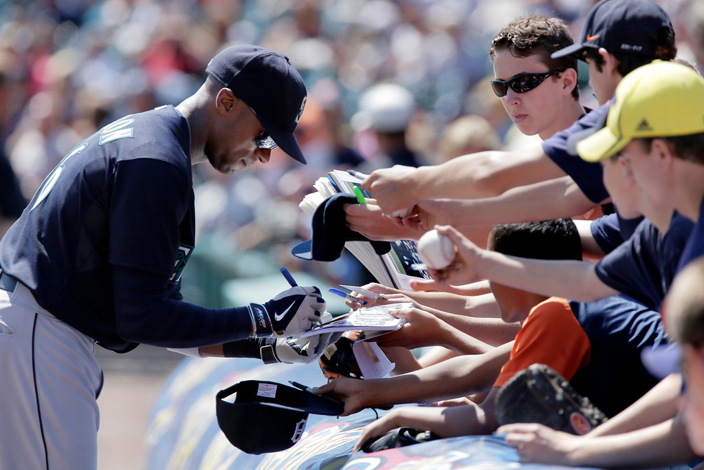 . Seattle Mariners\' Austin Jackson signs autographs for fans before a baseball game against the Detroit Tigers on Sunday, Aug. 17, 2014, in Detroit. (AP Photo/Duane Burleson)