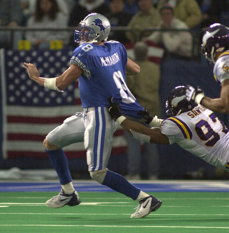 . Detroit Lions QB Mike McMahon tries to throw a pass while in the grasp of Minnesota Vikings Talance Sawyer during the Lions 27-24 win at the Pontiac Silverdome Sunday December 16, 2001.