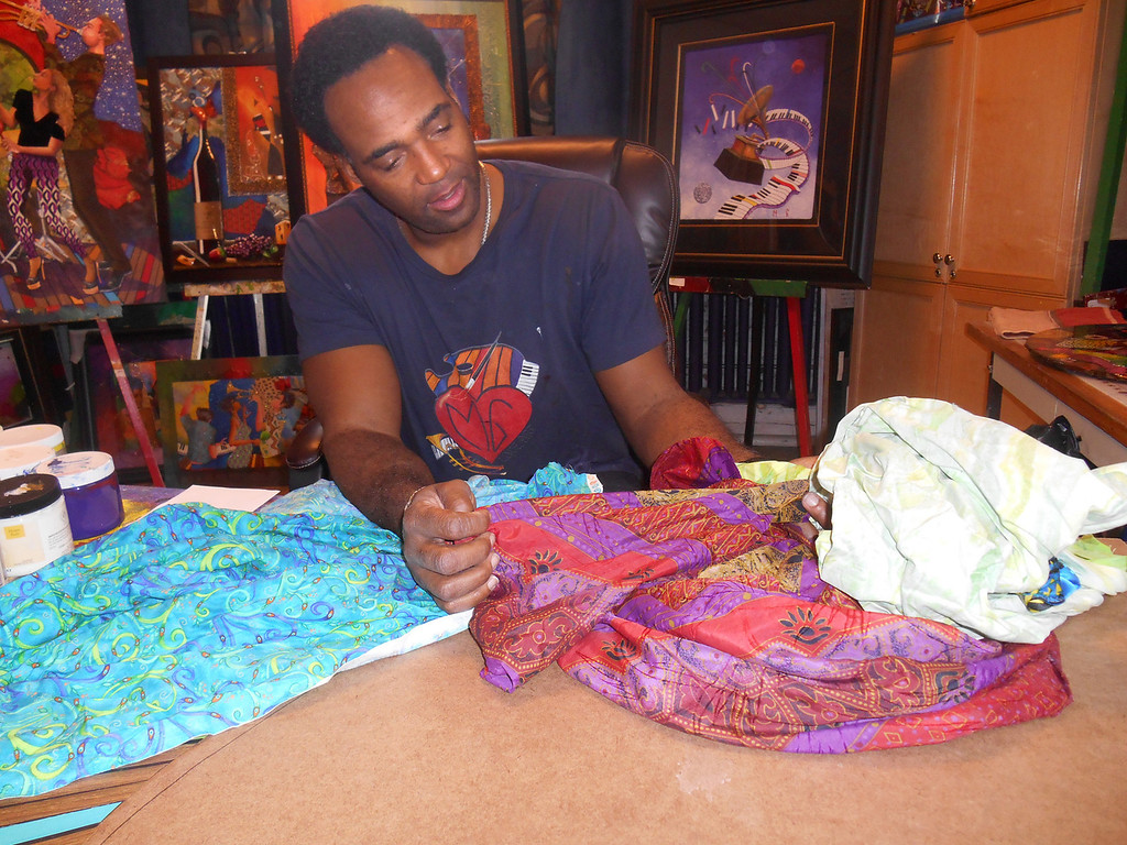 . Southfield artist Marcus Glenn looks over swatches of fabric that he will use in his Flat Life pictures. Photo by Nicole M. Robertson
