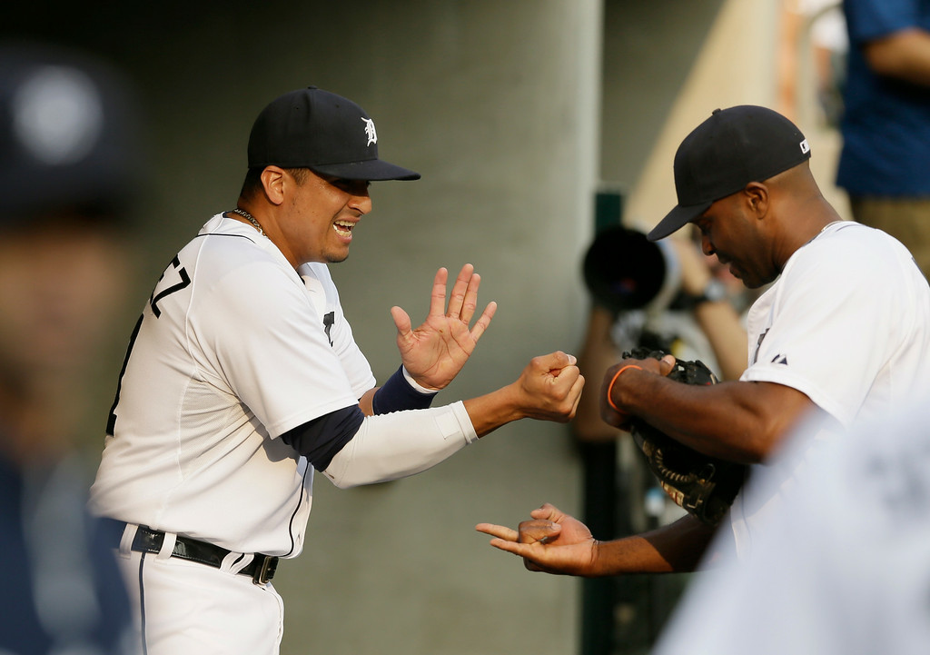 . Detroit Tigers designated hitter Victor Martinez, left, and right fielder Torii Hunter exchange handshakes in the dugout before the first inning of an interleague baseball game against the Colorado Rockies, Friday, Aug. 1, 2014, in Detroit. (AP Photo/Carlos Osorio)