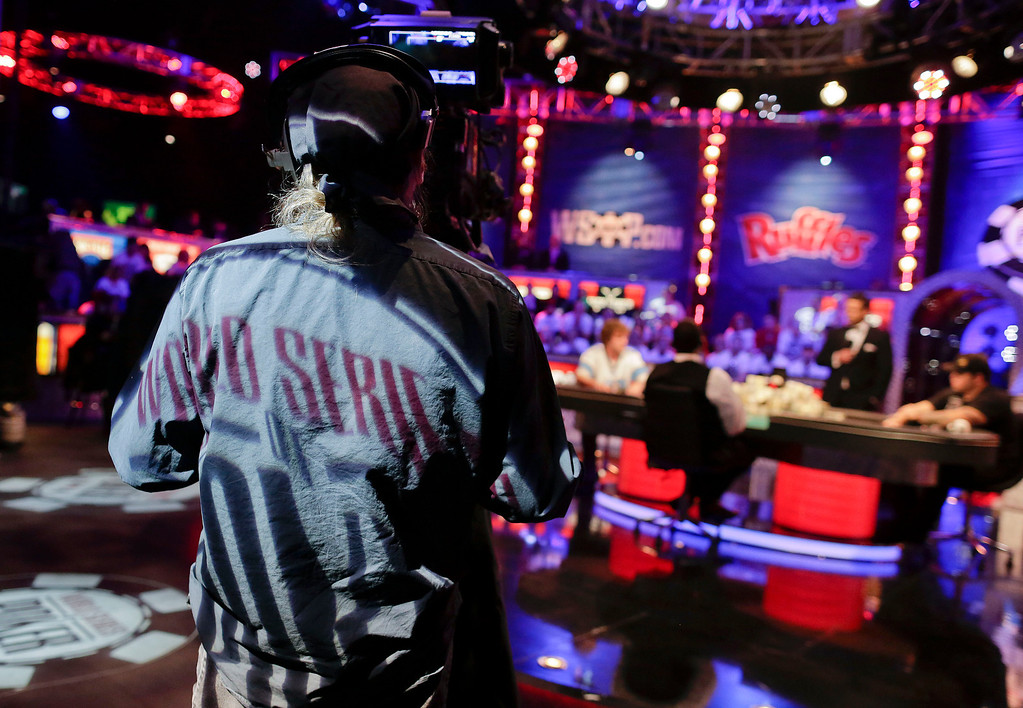 . The World Series of Poker logo is projected on the back of an ESPN camera operator during the World Series of Poker final table, Tuesday, Nov. 5, 2013, in Las Vegas. (AP Photo/Julie Jacobson)