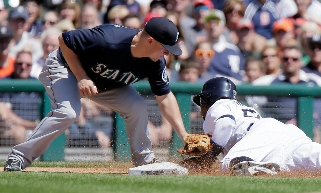. Detroit Tigers\' Rajai Davis, right, beats the tag from Seattle Mariners\' Kyle Seager to steal third base during the third inning of a baseball game Sunday, Aug. 17, 2014, in Detroit. (AP Photo/Duane Burleson)