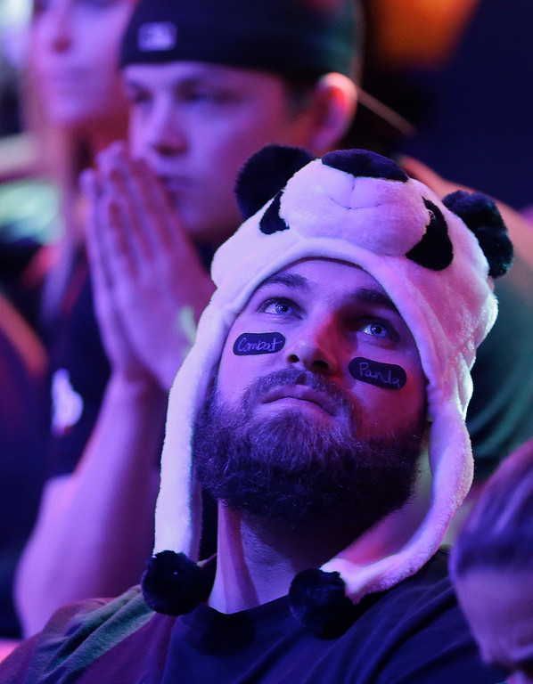 . A supporter for Jay Farber checks the scoreboard in the final hands of the World Series of Poker Final Table, Tuesday, Nov. 5, 2013, in Las Vegas. Farber, one of two remaining finalists, was defeated by Ryan Riess. (AP Photo/Julie Jacobson)