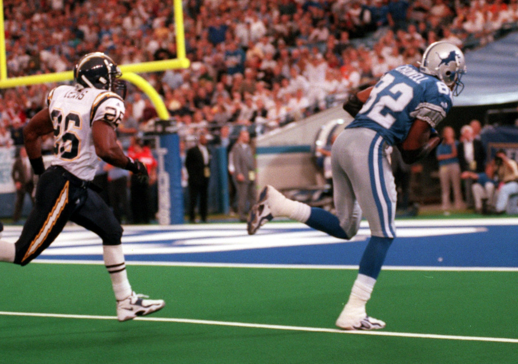 . Detroit Lions wide receiver Germane Crowell (right, #82) makes the reception and runs in for a touchdown as San Diego Chargers cornerback Darryll Lewis (#26) gives chase during first quarter action, Sunday, October 10, 1999.