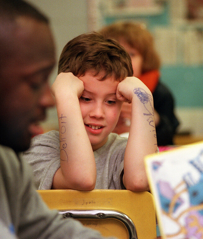 ". David Mikowski, 10,  listens to Detroit Lions running back Sedrick Irvin, reading to Dave Abbott\'s 4th grade class at Pine Tree Elementary School in Lake Orion.  Irvin was reading Dr. Seuss\' ""Oh, The Places You Will Go.\"""