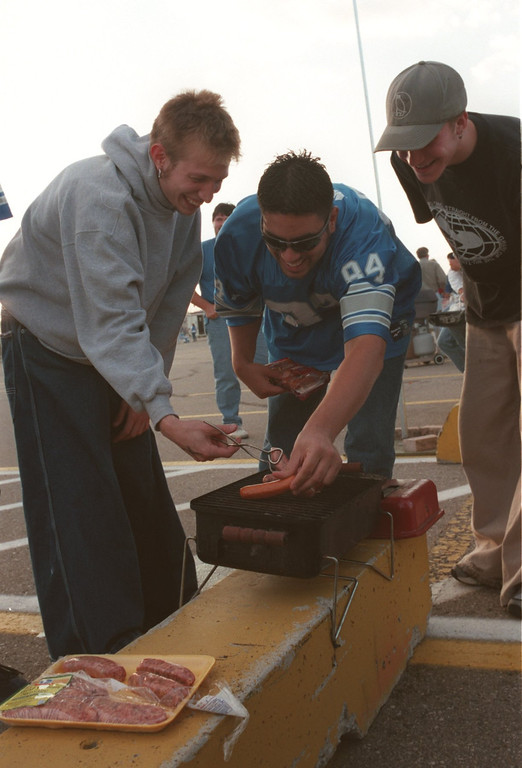 . Rick Childers, left, Joe Seidl, center, and Pedro Kemeza grill before the start of the Detroit Lions Monday nights game against the Tampa Buccaneers at the Pontiac Silverdome.